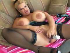 Busty blonde in stockings is fingering her puss